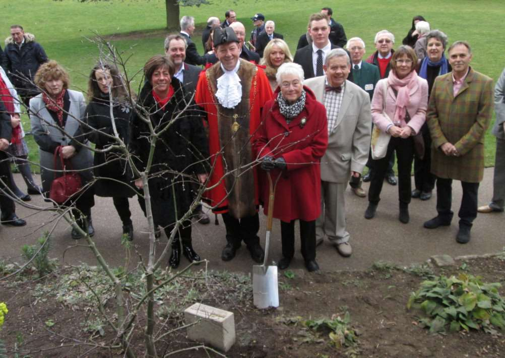 Mike Ames' daughter Anthea Ames and wife Monica with St Edmundsbury mayor Robert Everett in front of the tree planted in Mike's memory in Bury St Edmunds Abbey Gardens ANL-150320-113356001