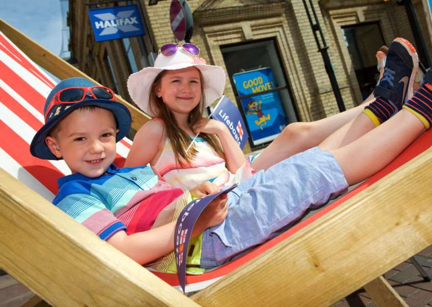 Bury St Edmunds, Suffolk. Whitsun Fayre - Theo and Ava Mitcham in a giant deckchair at the urban beach in the Traverse. ''Picture: MARK BULLIMORE
