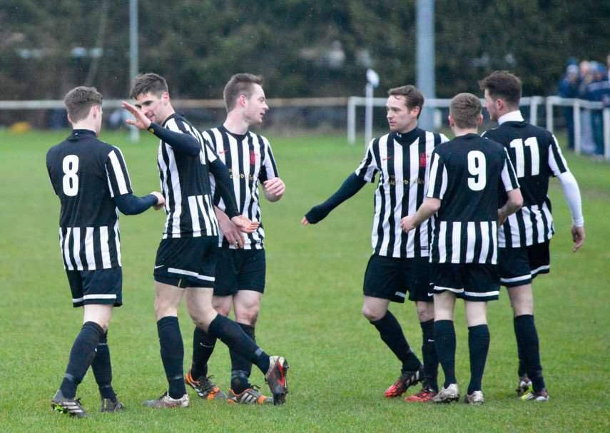 CELEBRATION TIME: Long Melford congratulate Jamie Griffiths, second left