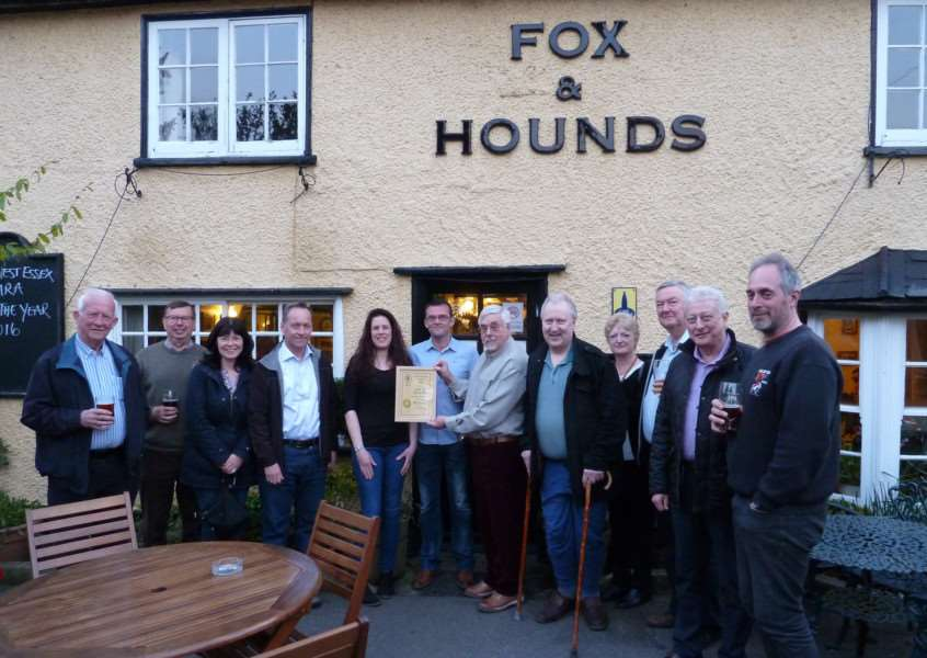 The Fox & Hounds licensees Rhiannon and Rob Carroll receive their North West Essex CAMRA Pub of the Year Award from Neil Hill (holding the certificate) and a few CAMRA members. ANL-160425-105410001