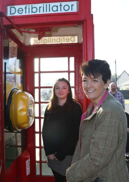 (L-R)Ruby Last and Jo Churchill MP officially open the new defibrilator in the village phonebox in Beyton. ANL-161022-185246009