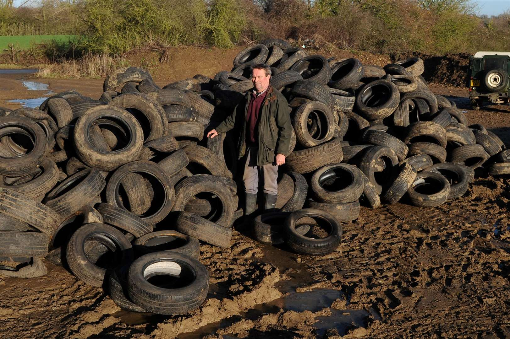 Hundreds of tyres have been fly-tipped on a farm in Milden....Pictured: Farmer Christopher Hawkins standing next to the huge pile of tyres on the farm.....PICTURE: Mecha Morton... (6791067)
