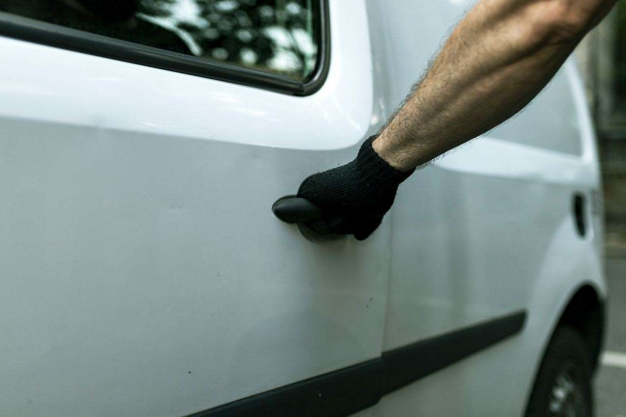 A burglar with black gloves trying to enter and steal a vehicle. Stock photo