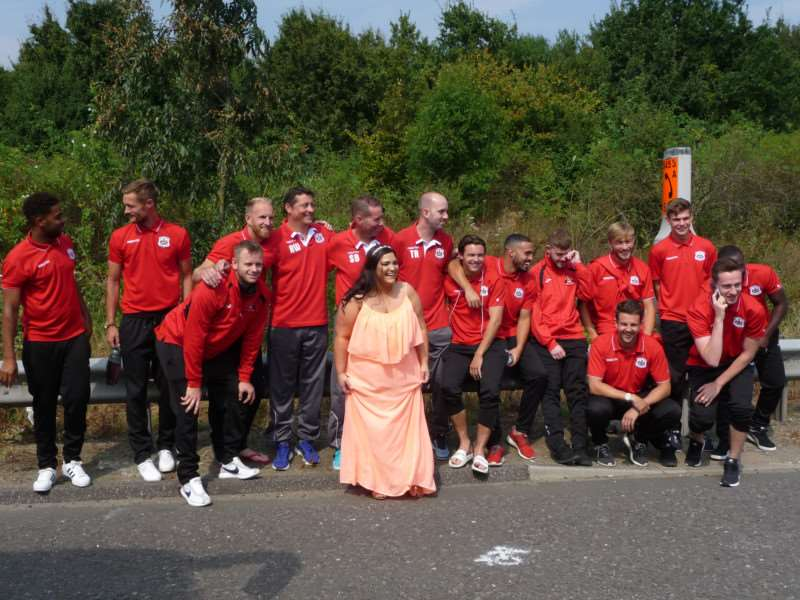 Mystery bride Lisa Cobbold pictured with Needham Market Footballl Club manager Mark Morsley and his 1st Team Squad by the central reservation of the M20 in Kent last Saturday
