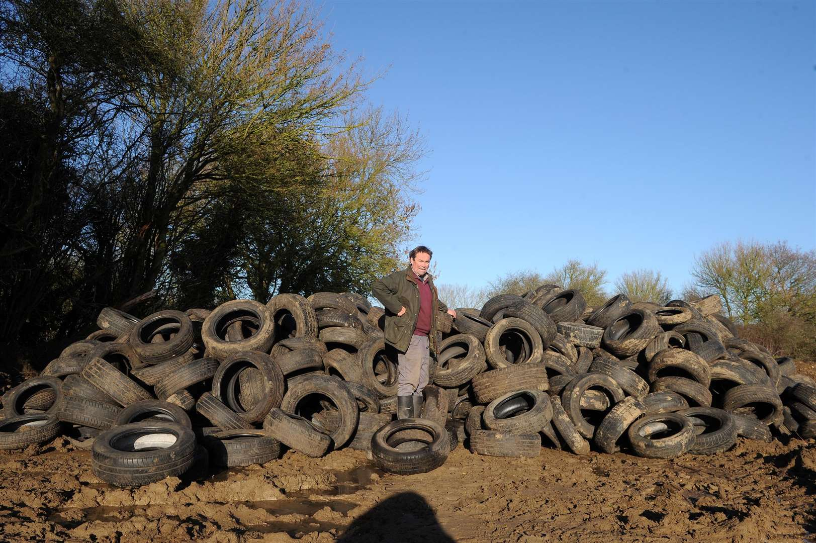 Hundreds of tyres have been fly-tipped on a farm in Milden....Pictured: Farmer Christopher Hawkins standing next to the huge pile of tyres on the farm.....PICTURE: Mecha Morton... (6791073)