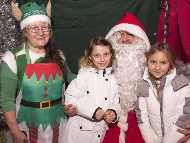 Maya Stolarz and Amelia Zablocka with Father Christmas and one of his elves at his grotto in St Andrews Church