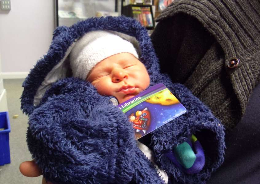 BABY READER: One-week-old Nathan Easting visited the Great Cornard library to sign up as a Suffolk Libraries member, receiving his first library card. ANL-151130-171301001