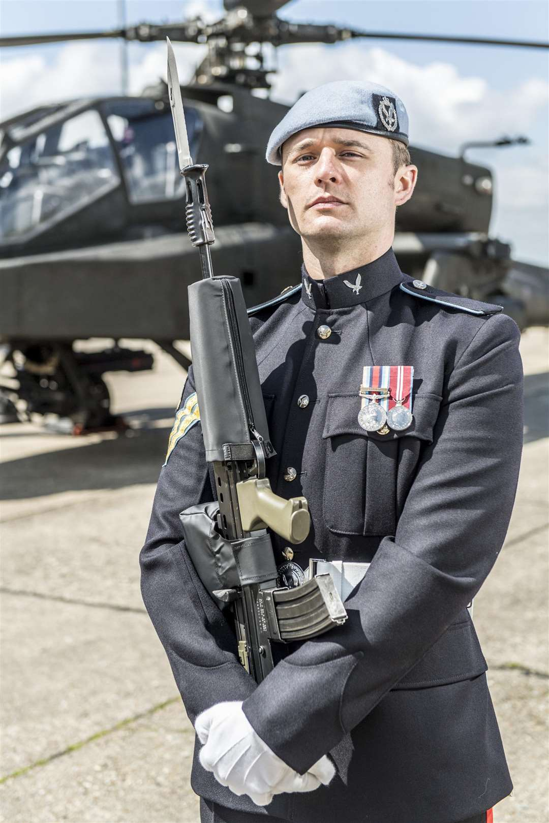 Corporal Stuart Armstrong, 27, from Glasgow, who's based at HQ Squadron, 3 Regiment Army Air Corps, Wattisham, stands proud in front of the Apache Attack Helicopter. Photographer:Corporal Ben Beale/ MoD Crown (1942067)