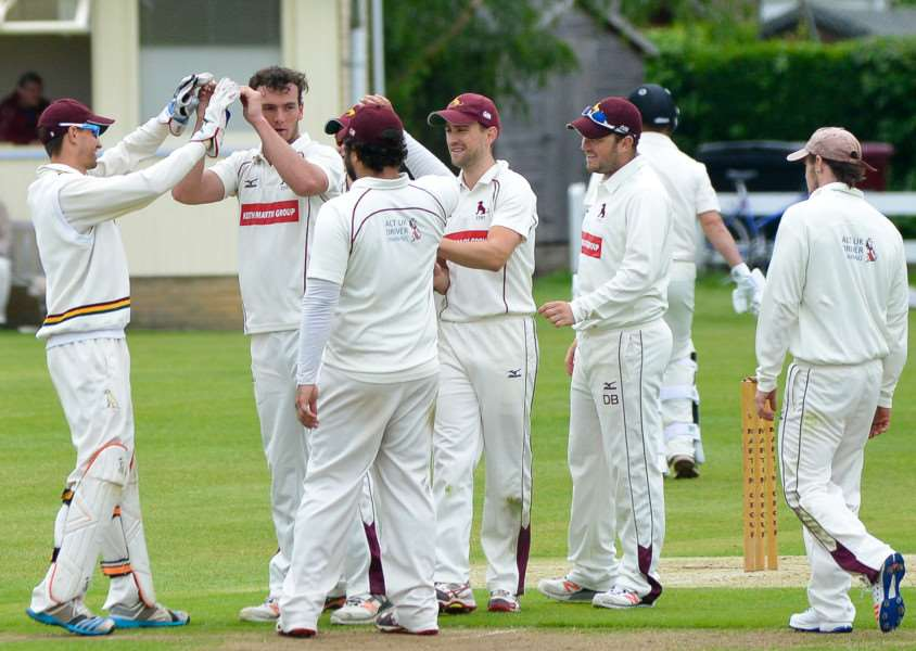 CELEBRATION TIME: Sudbury players come together in delight after claiming the wicket of Bury's Mark Nunn