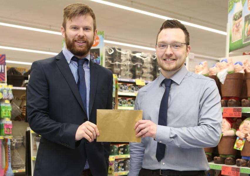 Manager of the new B & M store in Bury, Lewis Wilding, right, makes a presentation to George Chilvers from St Nicholas Hospice Care