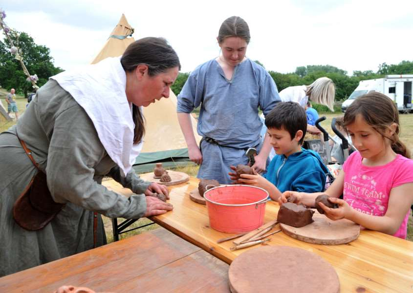 Dragon Festival at West Stow''Pictured; Owen (8) and Hannah (10) Jones making clay dragons, being taught by Viking Trader Theo and Viking Missionary AJ ANL-150621-233312009