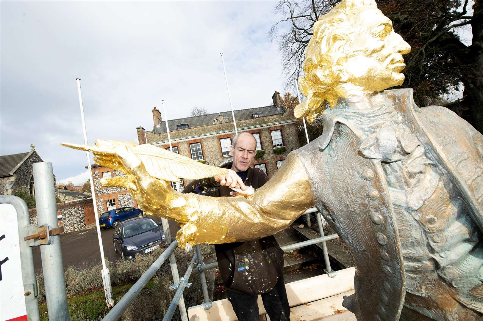 Artist Mark Harper who is currently regilding the Thomas Paine statue in Thetford	Picture by Mecha Morton.