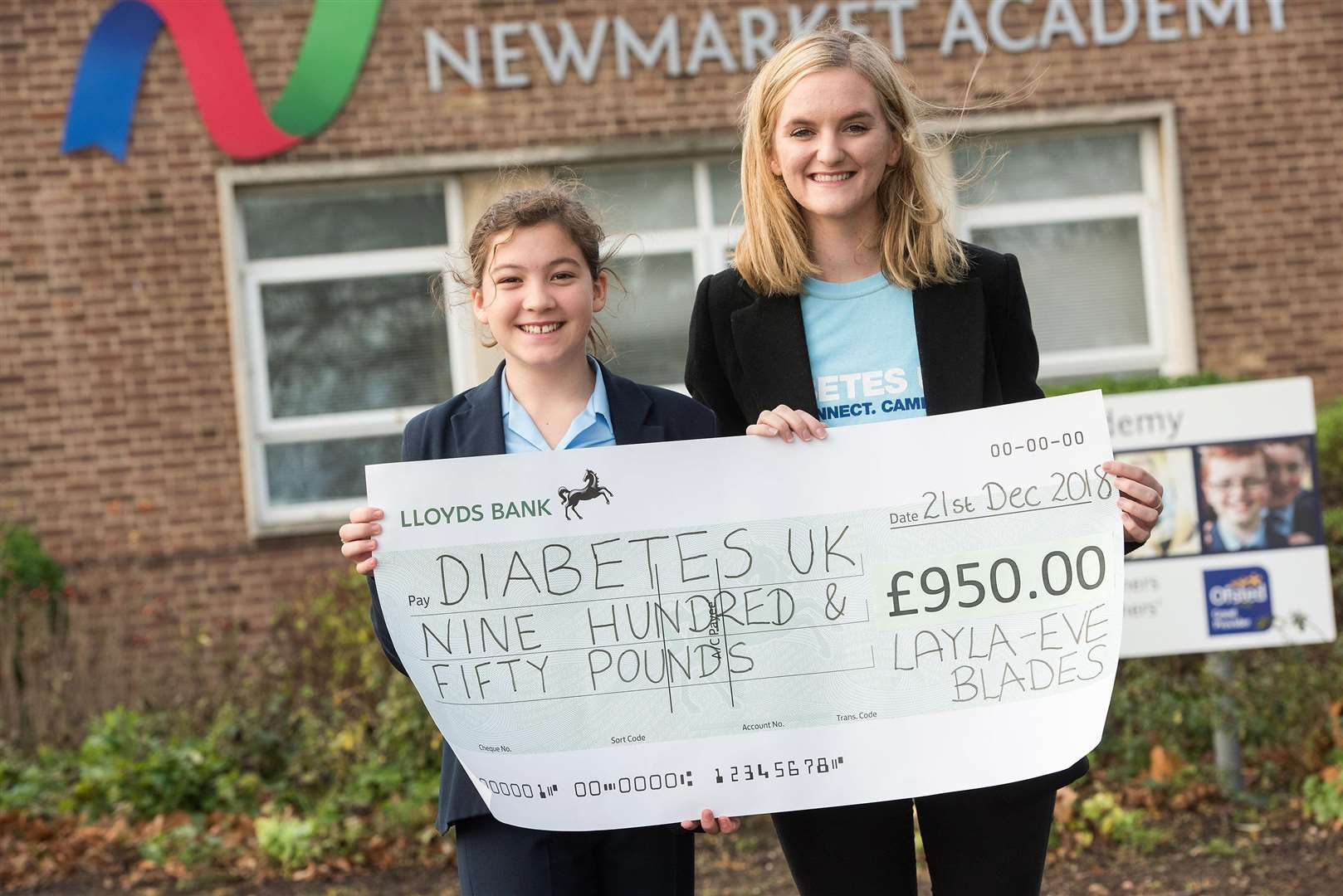 Newmarket Academy's Layla Blades presenting proceeds of a cake stall she organised to Diabetes UK volunteer Danielle Jones