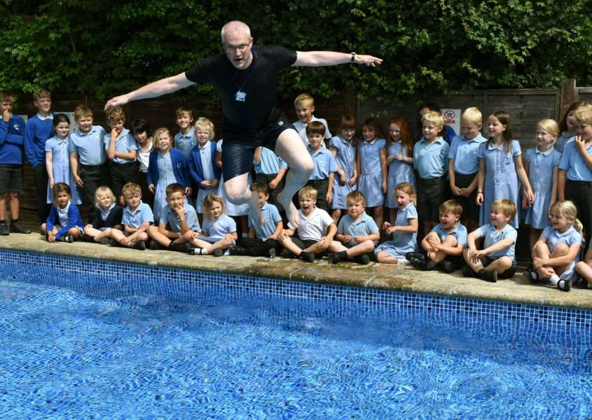 Hartest Primary School head Matthew Coombs take a big leap to officially launch the opening of the refurbished school swimming pool.