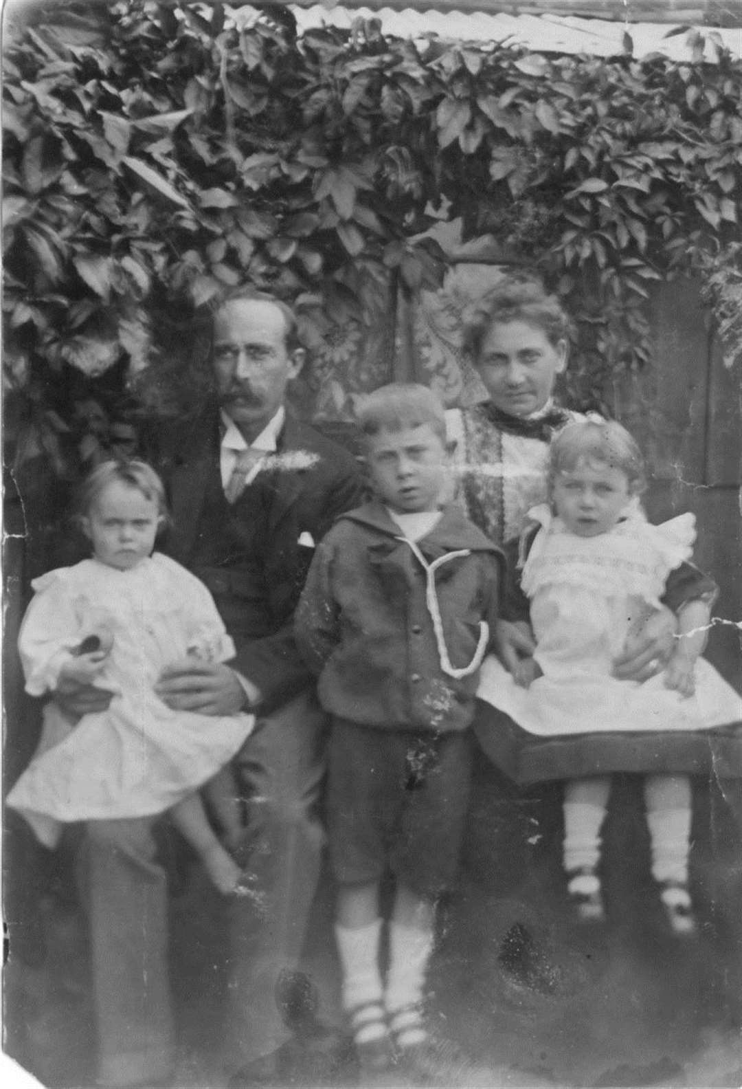 Family memories... Young Jack, aged six in his Sunday best with his parents John and Priscilla and sisters Ella and Bertha outside their Bakers Row cottage and right, the photograph of the cross initially placed on Jack's grave, the only evidence his parents had of their son's final resting place