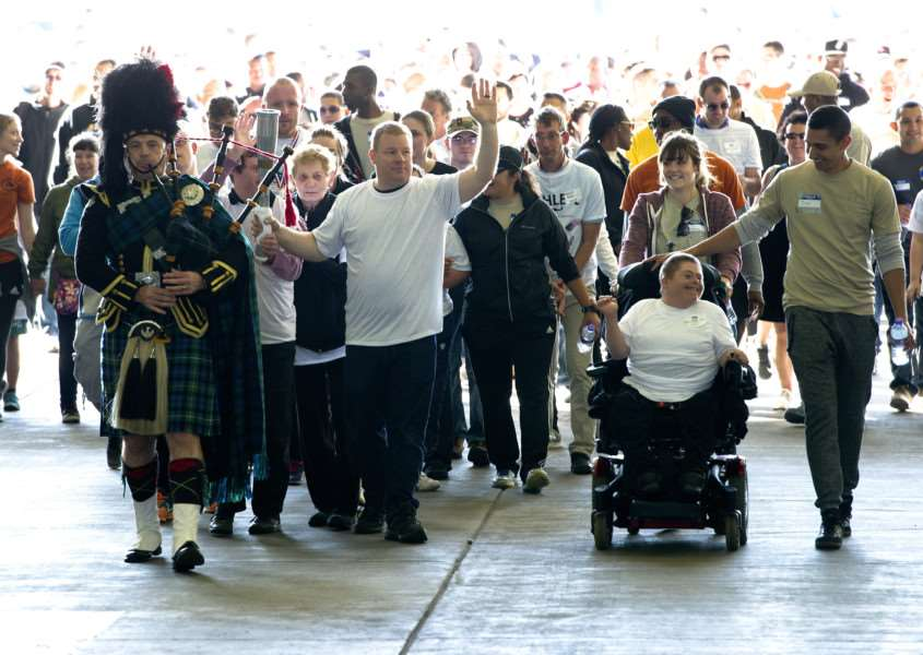 A piper leads the parade of athletes into the hangar 'sports stadium' for the event ANL-160926-001711009