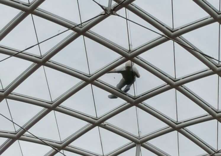 Isaac Moore, 27 on the glass roof of the Grand Arcade shopping centre