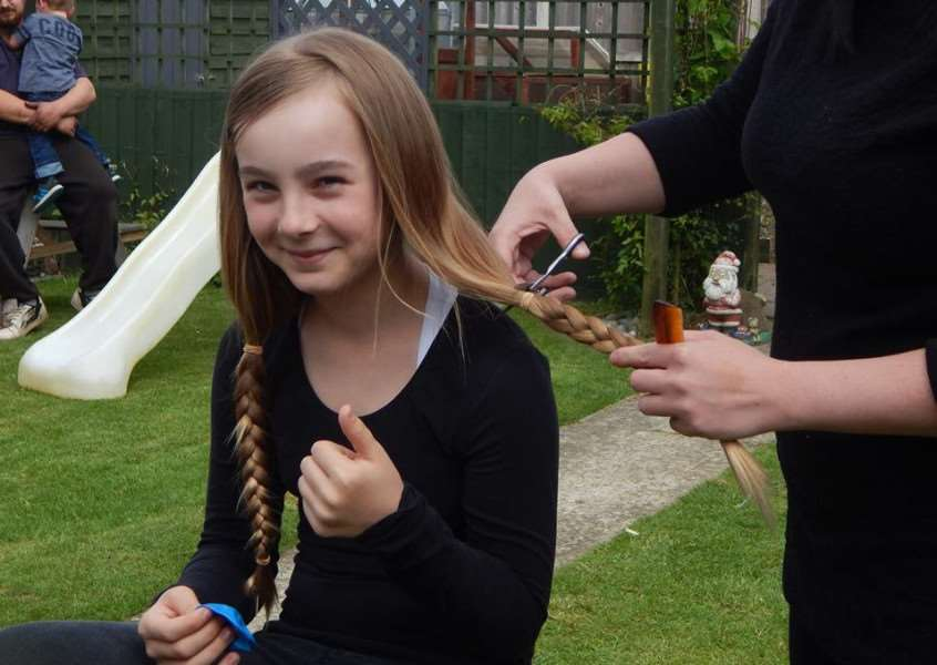 Ellie Biggadike, 11, had 12 inches of her hair cut off for charity. ANL-160525-111121001