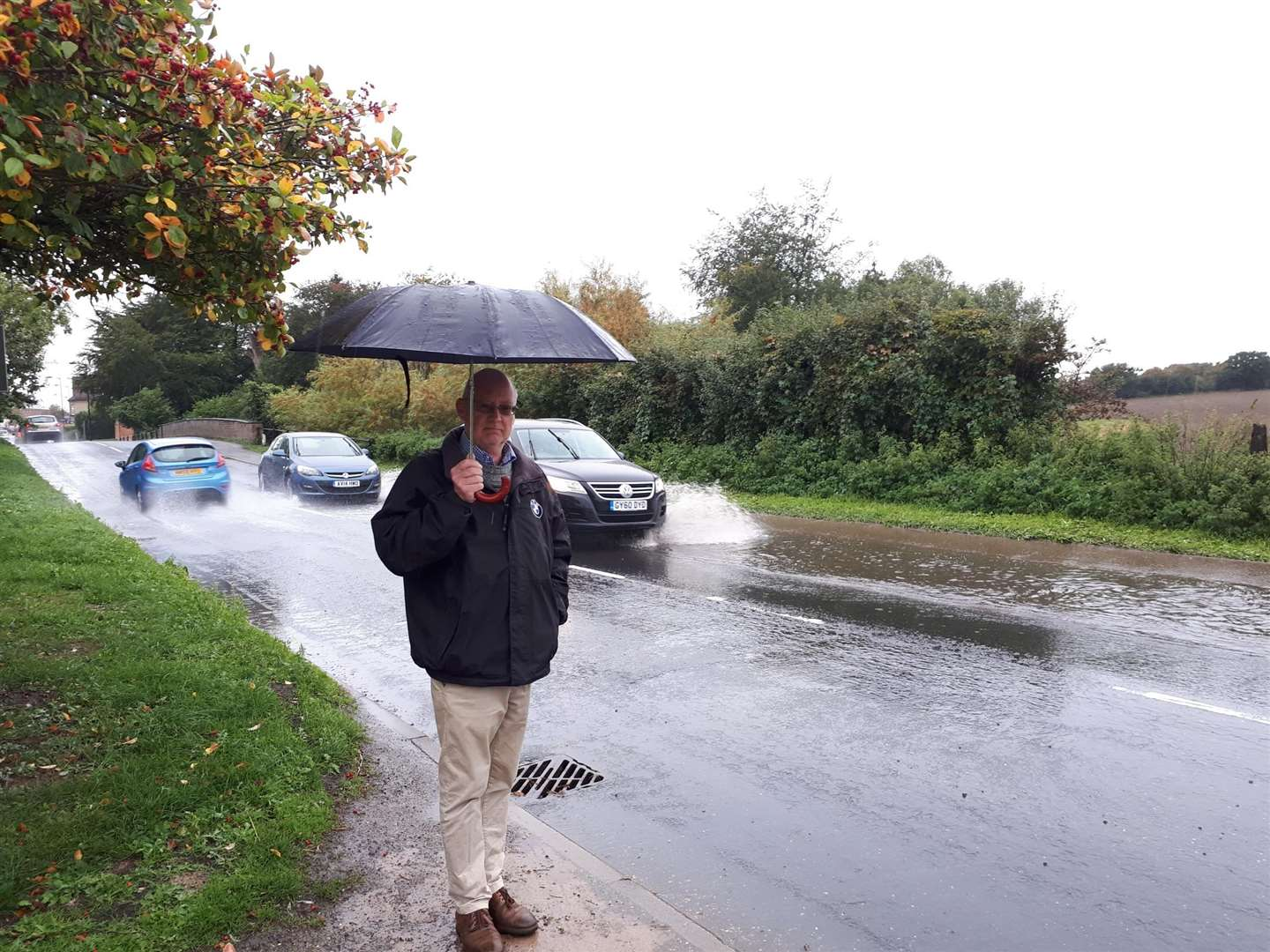 Cllr John Nunn, parish and district councillor for Long Melford, overlooks flooding in Hall Street, caused by a recurring blocked drainage issue. Submitted picture. (4527837)