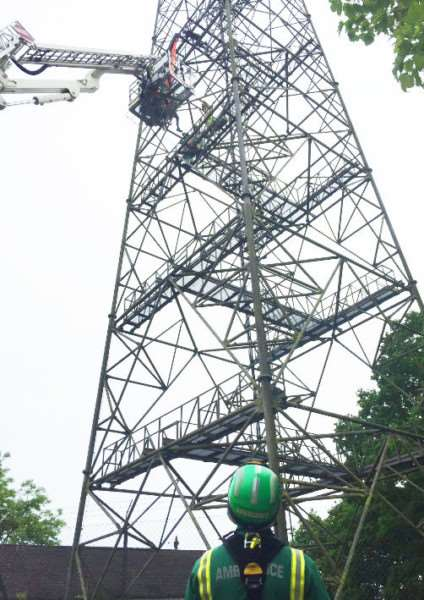 Emergency teams try to rescue two parachutists stuck 60ft up a tele communications mast. ANL-160523-121741001