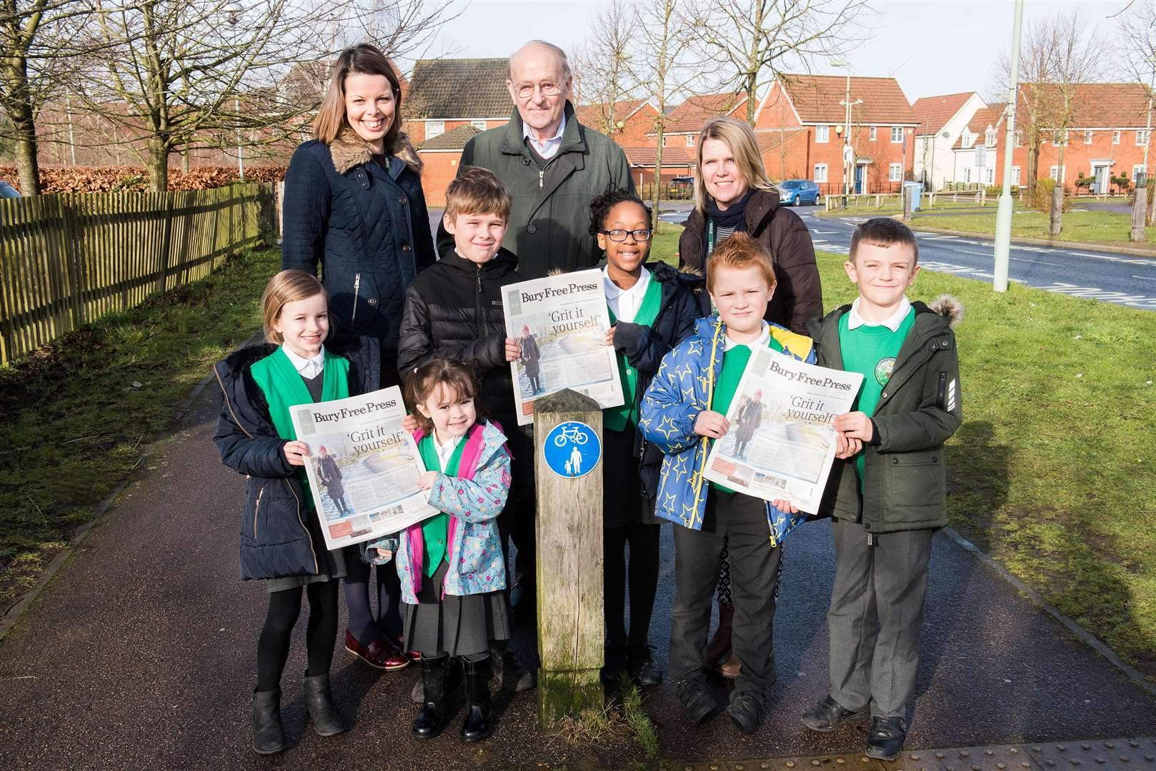 Cllr Trevor Beckwith with Ang Morrison, headteacher, Jo Uttley deputy headteacher and pupils outside the front gates where the icy path was last week. Picture Mark Westley.