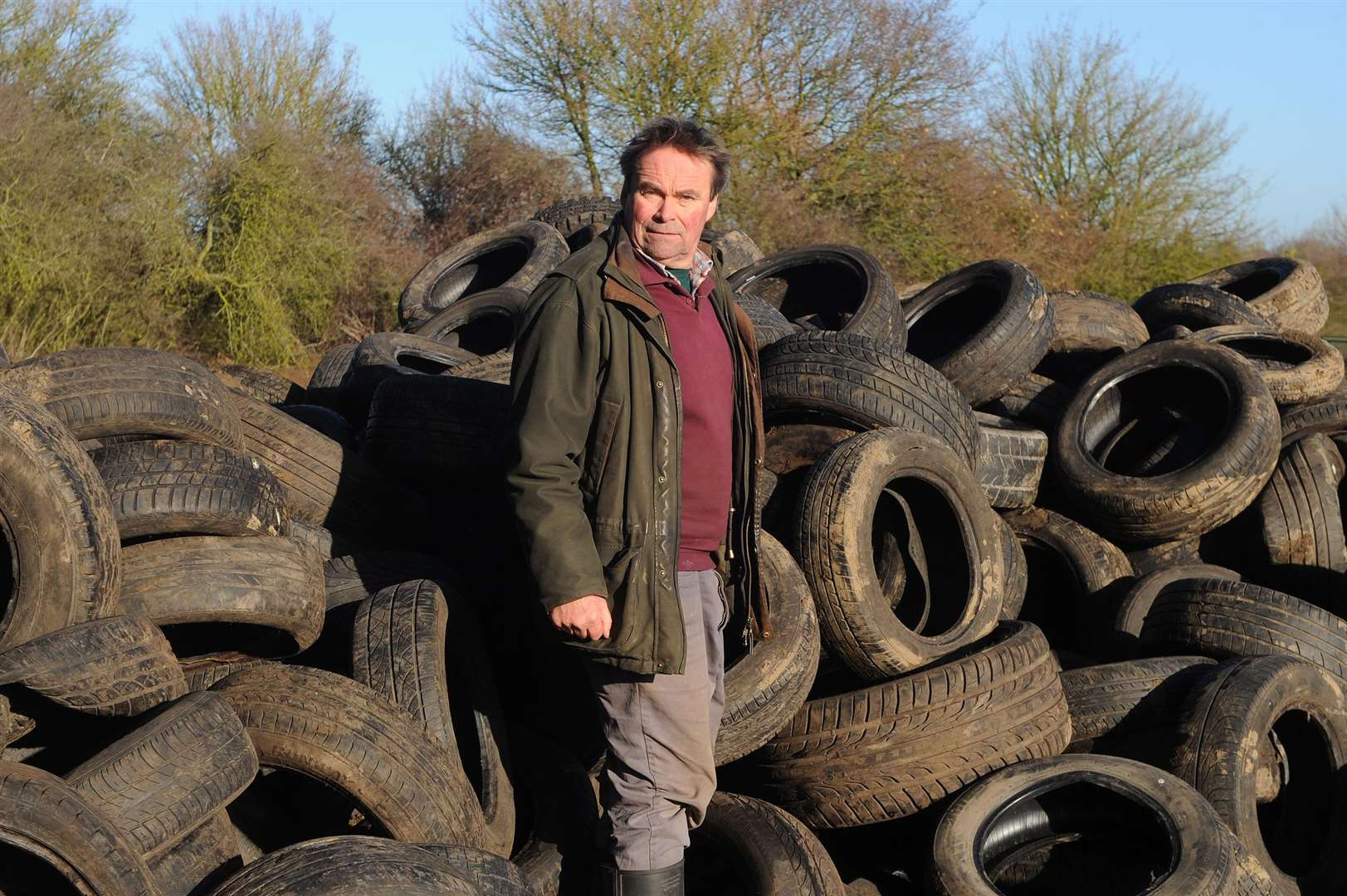 Hundreds of tyres have been fly-tipped on a farm in Milden....Pictured: Farmer Christopher Hawkins standing next to the huge pile of tyres on the farm.....PICTURE: Mecha Morton... (6791070)