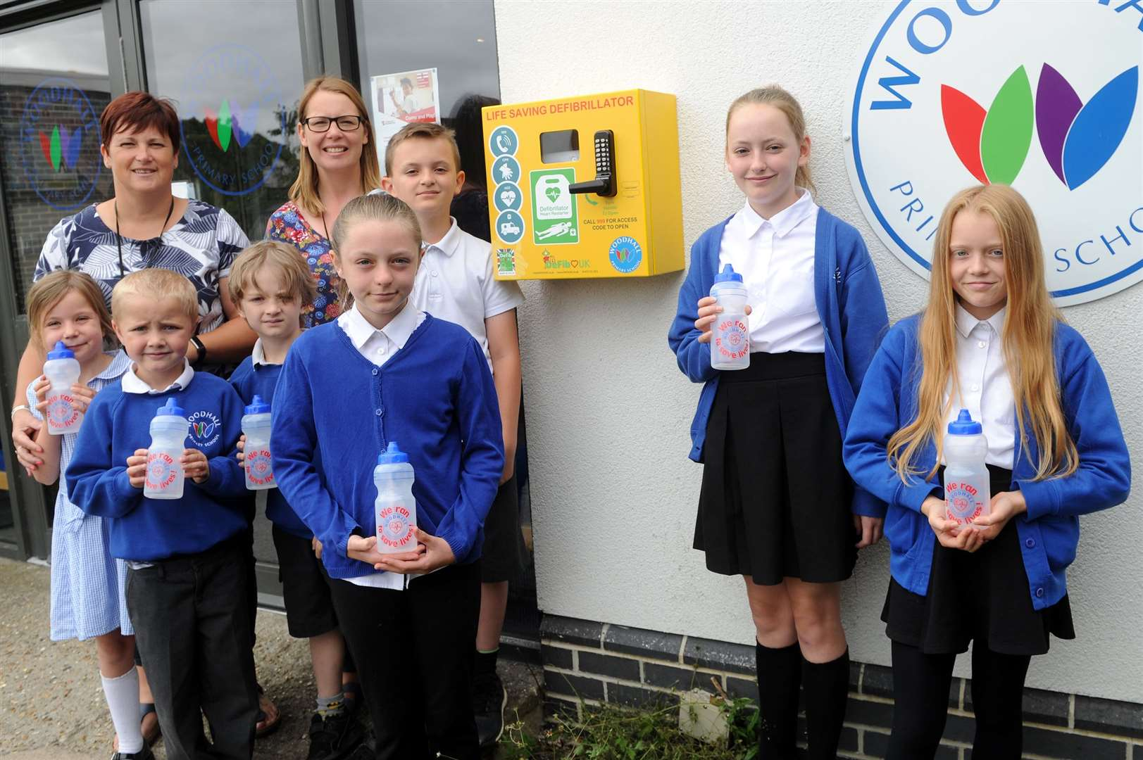 Pupils at Woodhall Primary School in Sudbury raised £8,000 to fund a defibrillator on the school premises, which is available for use by the whole community...Pictured: Pupils along with Sian Guyton (LSA) and Pamela Adams (HLTA)...PICTURE: Mecha Morton. (13842143)