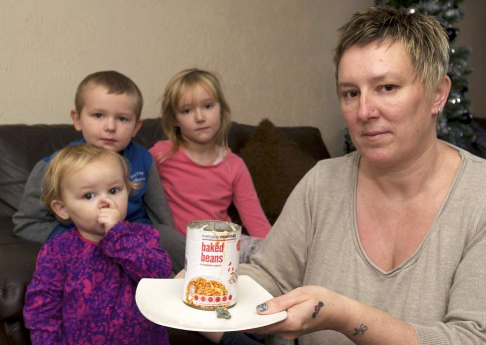 BURY: Mum Michele Seeley is unhappy after finding mould in a tin of baked beans as she was preparing tea for her three children pictured is Michele Seeley holding the beans with Raya Stevenson, Kyler Stevenson and Tahlia Stevenson. ANL-141222-202310009