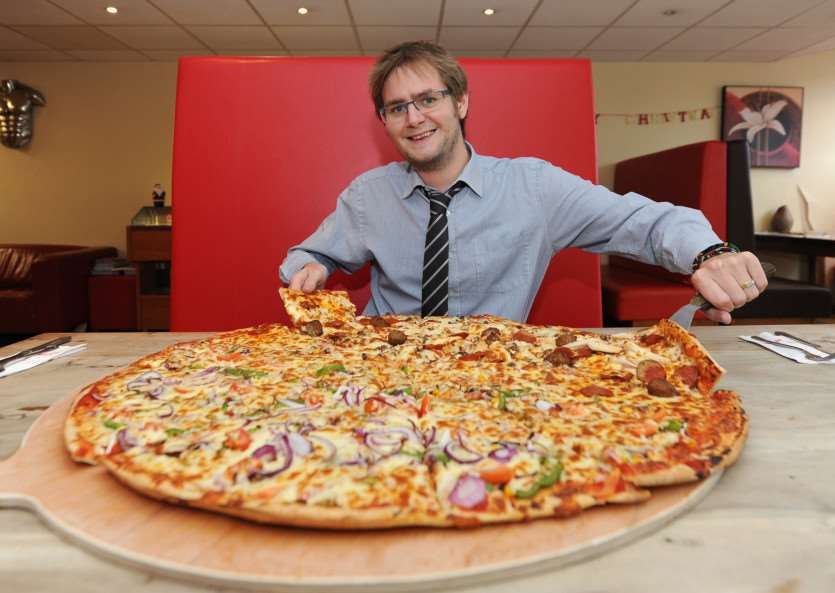 Biggest pizza in Bury? - at Pizza Town''Pictured: Bury Free Press reporter, Adam Howlett, trying the 28 inch pizza ANL-140812-070922009