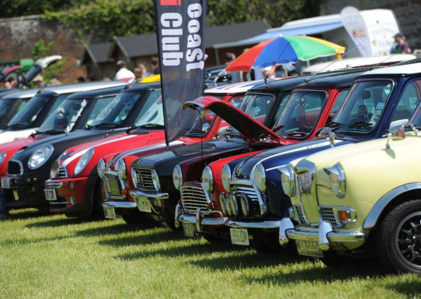 Minis through the ages from the upmarket 1969 Riley Elf in the foreground to modern BMW Minis ANL-160606-092358009