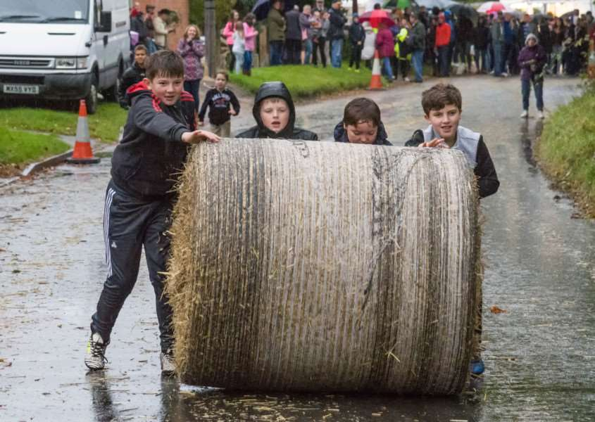 The bale push saw men, women and children push their straw through the wet weather