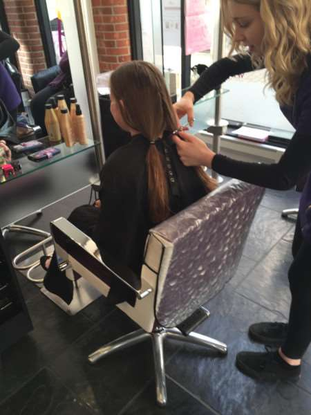 Ella Johnson, 12, had her hair cut as part of hairdressing student Sarah Picken's charity event ANL-161204-162235001