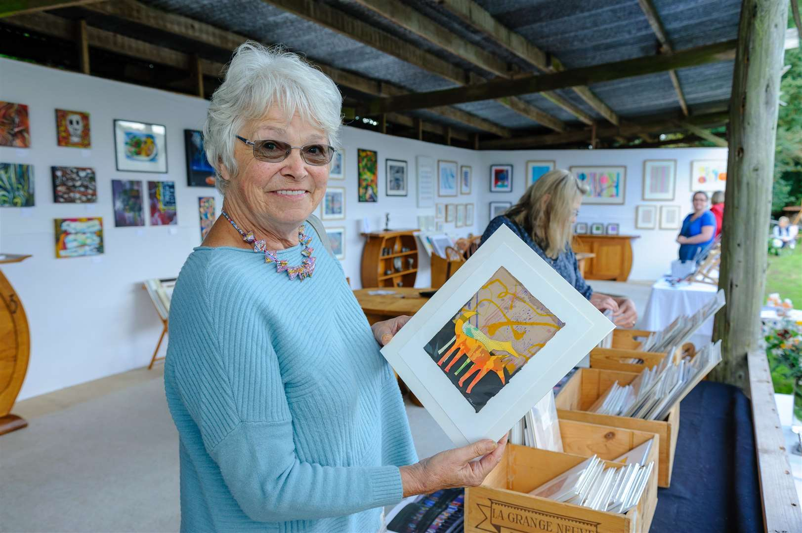 Polstead, Suffolk, 25 August 2018..Polstead Exhibition which took place over the bank holiday..Held in the grounds of Maria Martin's Cottage, artists and makers will be showcasing their wares from furniture to bespoke bird boxes. Christa Grounds looking with a print for sale...Picture by Mark Bullimore Photography. (3803120)