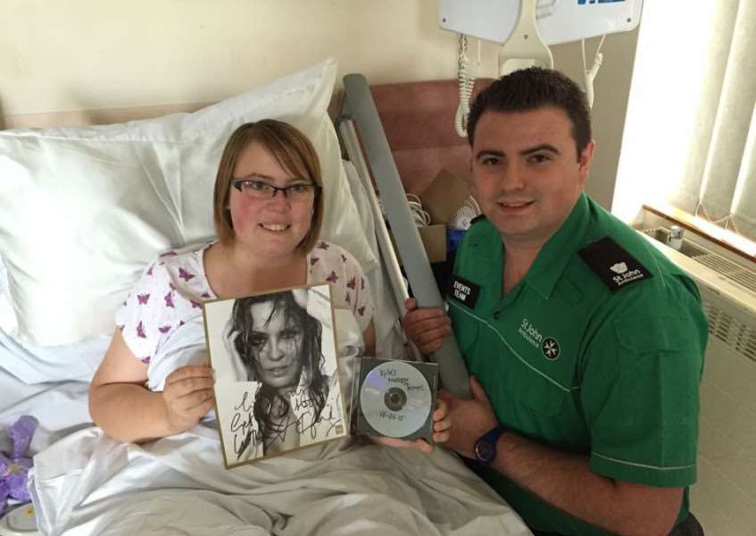 Bryony Charles receives a video message and signed picture from Kylie Minogue - presented by St John Ambulance colleague Alistair MacKay ANL-150622-155948001